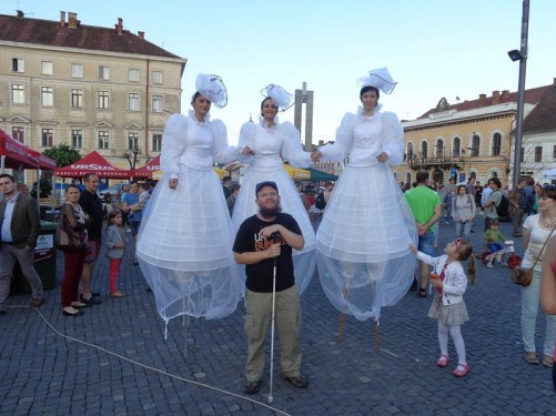 Tony in front of three young ladies in white wedding dresses on stilts. Many locals were dressed in costumes as part of Cluj Week, which included live opera and/or traditional orchestral music and performances on a large stage in Union Square.