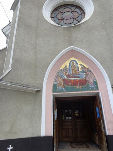 The main doorway into the Assumption of the Virgin church. A circular window above. This orthodox church dates from 1892. Inside there are icons by well-known Maramures painter Traian Biltiu Dancus.
