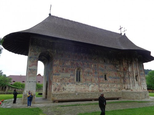 View of the church's exterior with the walls almost completely covered with frescoes. These frescos of amongst the best preserved of the eight painted churches. The dominant colour of the frescoes is a reddish brown with patches of blue. The eaves of the roof have a large overhang to help protect the paintings beneath from the weather.