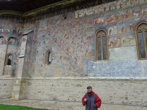 Tony at the Church of the Resurrection at Sucevița Monastery. Located in the village of Sucevița, 18 kilometres (11 miles) from the city of Rădăuţi. The monastery was built in 1585, but the paintings date from around 1601, which makes Sucevița one of the last churches to be decorated with the famous exterior paintings. In view, the paintings include rows of angels ascending a ladder (Jacob's Ladder), as well as other Biblical scenes.