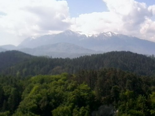 Excellent view of forested hills from Râșnov Fortress. The snow-capped Carpathian Mountains away in the distance.