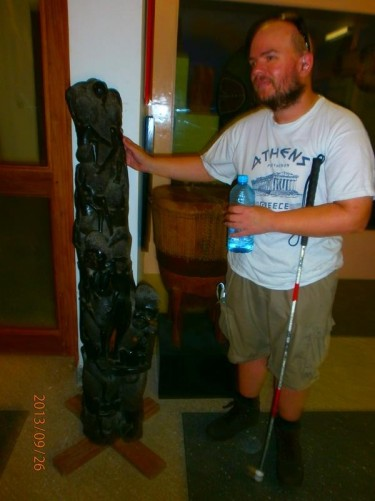 Tony touching a piece of traditional artwork. This tall narrow wooden-carved object, standing on the floor, includes several traditionally dressed human figures.
