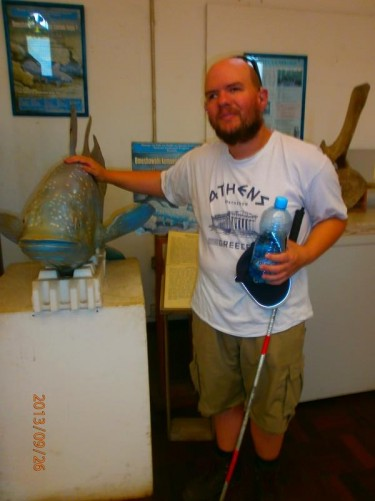 Tony touching a model of a large fish inside the museum. Part of a display about the local marine environment.