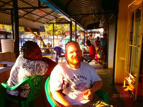 Tony at a chip and egg shop close to Zebra Bar with local couch surfer and traveller, Mericky, whom he stayed with. A local woman looking over from a table along side.