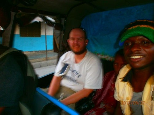 Tony in the back of a Tanzanian taxi next to a local woman and child.