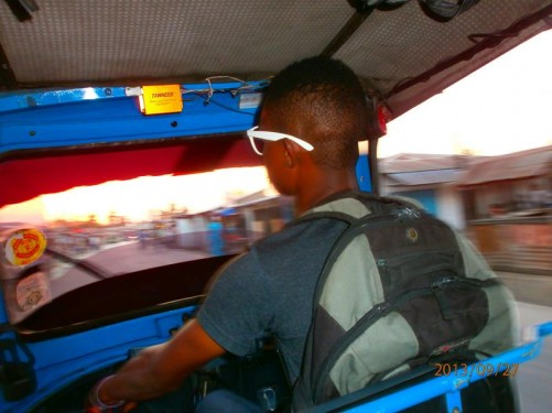 View from the back seat of the taxi. A young man driving in front and a blurry view of the road ahead with the yellow glare of the sun setting.