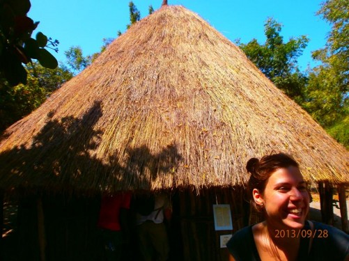Outside one of the huts. This one has a straw roof and beneath an outer wall made from narrow tree trunks and branches.