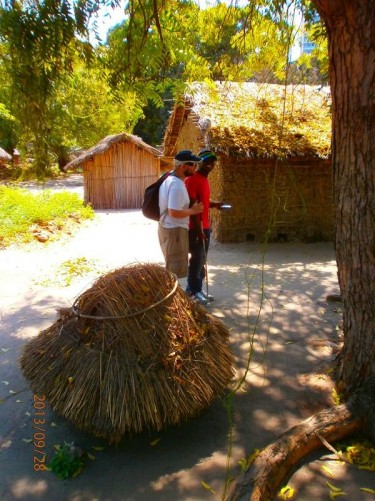 Tony with Mericky. In front of the camera, a worked bundle of straw tied together with a rounded top, and probably intended to cap the middle of a round straw roof. A rectangular hut can also be seen opposite.