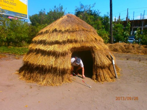 Tony crawling through the low doorway of a different round hut. This one is again completely covered with straw.