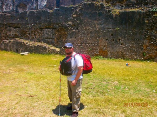 Tony at the Old Fort. He's stood in a grassy area within the fort with the ruins of a high stone outer wall behind.