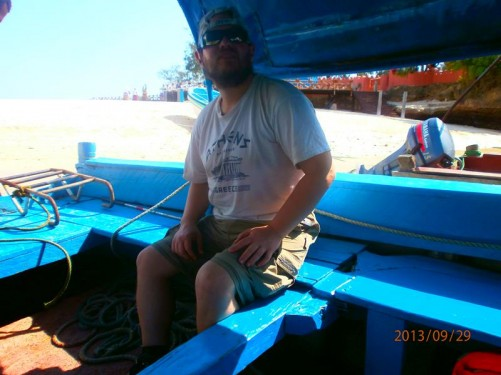 Again Tony waiting in the dhow. A view along the sandy beach in the background.