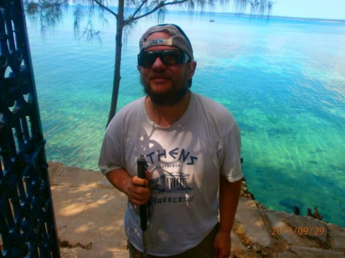 Tony standing in another doorway with a pleasant view of the turquoise coloured Indian Ocean in the background.