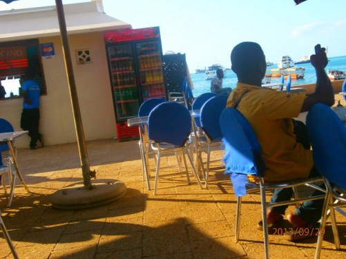 Back in Stone Town near the harbour at an outdoor café. Boats of various sizes are just visible in the sea behind.