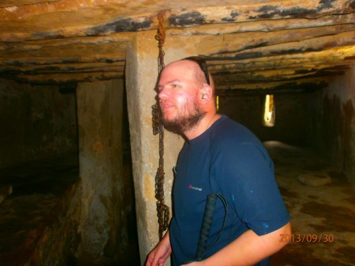 Slave Chamber. Tony in a bare underground room with chains hanging from the ceiling. Slaves were kept here before being sold at the slave market.