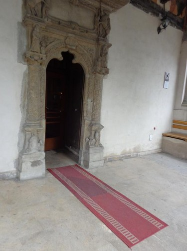 Inside the front porch of Coltea Church, looking towards an inner entrance doorway decorated with stone carvings.