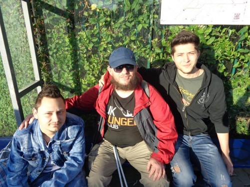 Tony sitting on a bench at a bus stop with two Romanian guys.