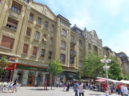 The tall elegant façades of buildings down the east side of Victory Square. They today house shops on their lower floors.