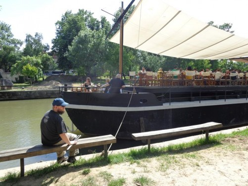 Tony sitting on a bench by the Bega River. A river barge, now being used as a restaurant, moored in front.