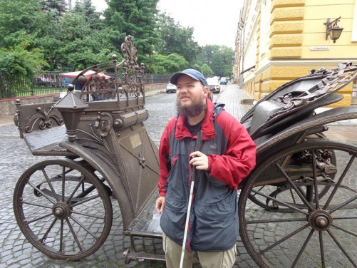 Tony next to an historic carriage on Olha Kobylianska Street. The horse-drawn carriage is made mostly of iron. Olha Kobylianska Street is a wide pedestrian street paved with cobblestones, which runs south from Central Square. It contains many historic buildings.
