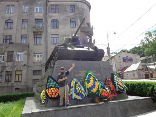 Tony standing on the front of the Monument of the Red Army in World War II. A Red Army tank raised on a stone base.