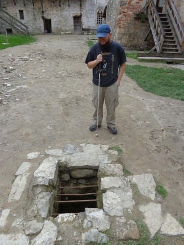 In the fortress's inner courtyard. Tony in front of a hole in the ground, probably a well.