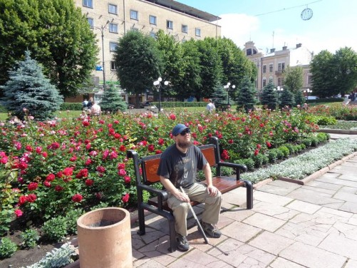 Tony sitting on a bench in Theatre Square. A flower bed full of roses behind.