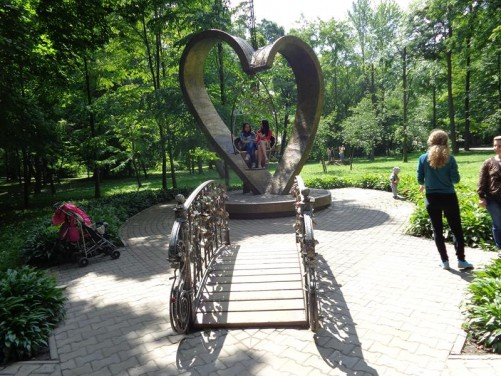 Shevchenko Central Park of Culture and Leisure. In front a heart-shaped sculpture with a seat suspended in the middle.