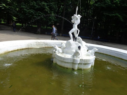 A fountain with a sculpture in the middle. The sculpture includes a human figure surrounded by frogs with water spraying from their mouths.