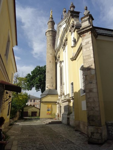 In a cobbled street outside the Roman Catholic Cathedral of Saints Peter and Paul. Unusually there is a minaret attached to the front. This dates from the 17th century when the Ottomans controlled the city and turned the church into a mosque.