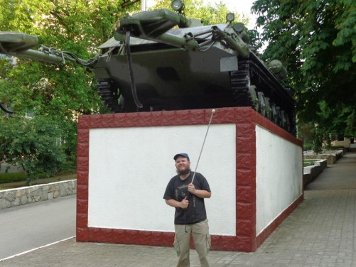 Tony in front of a Soviet mine sweeper tank raised up on a platform.