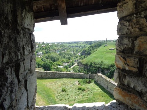 View from a rectangular opening through the castle's stone walls towards the river gorge.
