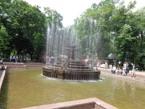A large pond with a fountain in the middle in Stephen the Great Park. The fountain is circular with many jets of water spraying up into the air.