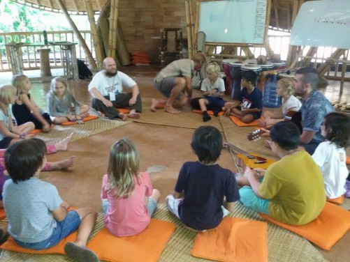 Tony with the school children and teachers sitting in a circle on the floor playing drops.