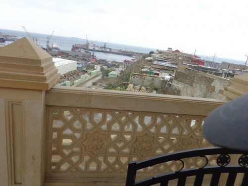 Looking down from the mosque's courtyard to a harbour below. Ships docked with large cranes for moving cargo.