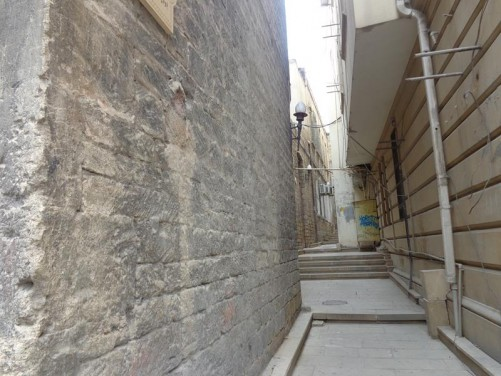 View along a narrow backstreet. Stone walls of buildings at either side.