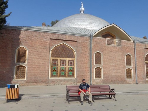 Tony sitting on a bench outside the Shah Abbas Mosque. This mosque dates from 1606, but it was totally reconstructed in 2008. It is built of red brick with a central silver-coloured dome.