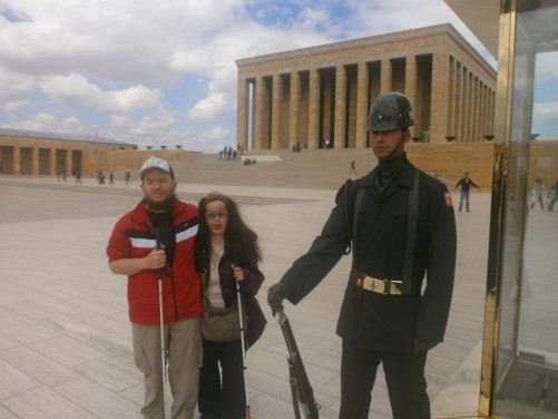 Tony and Tatiana next to a ceremonial guard standing along side a sentry box. The guard is dressed in dark green army uniform with a metal helmet and a rifle at his side. This is at the side of the large Ceremonial Plaza, which is 129 metres long and 84 metres wide. The Hall of Honour, containing Atatürk's tomb, is in the background.