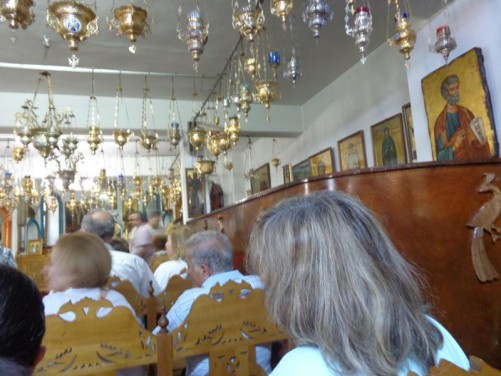 Inside the monastery church. Religious icons on the walls and metal vessels for burning incense (thuribles) hanging from the ceiling.