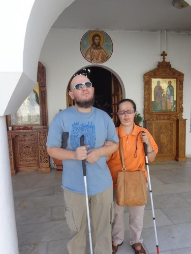 Tony and Tatiana standing outside a doorway at the Monastery of Agios Raphael.