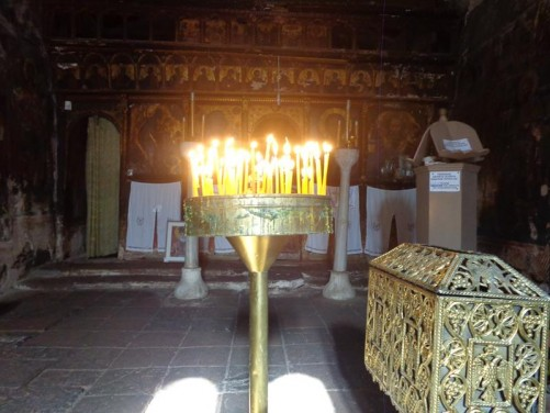 Inside the small church of Saint Nicolas (Agios Nikolaos) in Petra village. Candles lit on a stand in front.