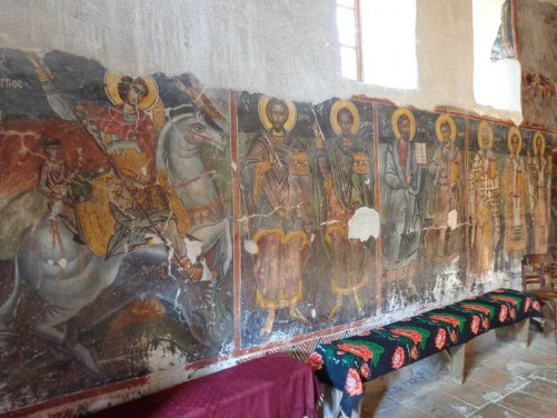 Colourful paintings along a wall inside Saint Nicolas church. The church's earliest frescos date from the 16th century.