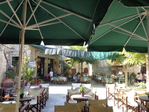 Mesta village square. Lined with stone buildings and shaded by trees. People relaxing at café tables.