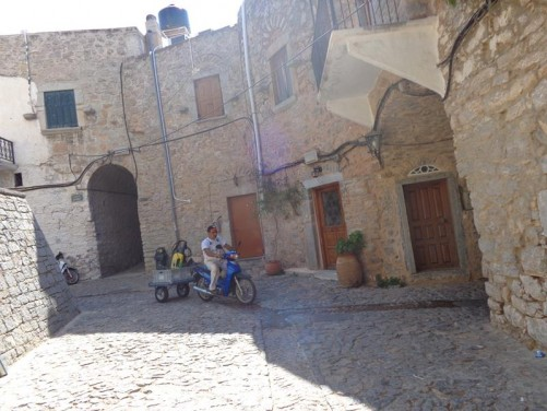A junction of cobbled streets in Mesta village. A man passing by on a scooter pulling a small trailer.