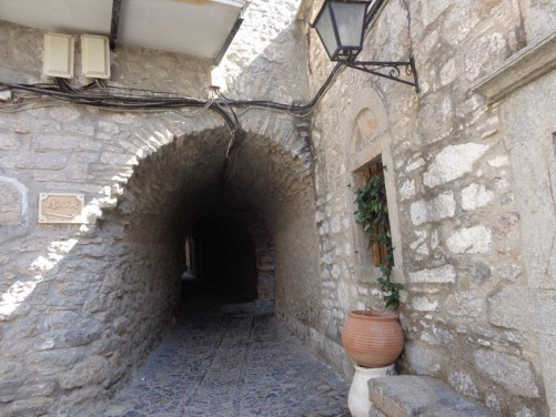 A narrow covered street with stone walls and arched roof. There are lots of these vaulted alley ways in the village.