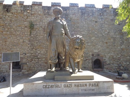 In front of a statue of Cezayirli Gazi Hasan Pasha (1714-1790), his hand on a lion, which stands alongside. He was a Ottoman admiral, who rose through the military ranks, having been bought as a slave by a Turkish merchant when he was a child. He was fleet commander during the Battle of Çesme against the Russians. The lion is said to have been a pet brought back from Africa.