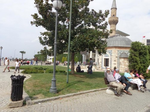 People sitting on benches in Konak Square with Yali Mosque again in the background.