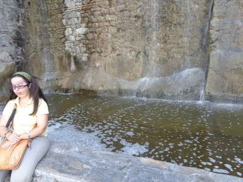 Tatiana sitting on a wall with water cascading into a pool behind.