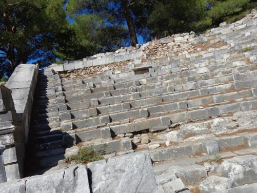 Rows of stone seating at the theatre. The seats form a horseshoe shape cut into the hillside. The theatre was first built around 340 BC.