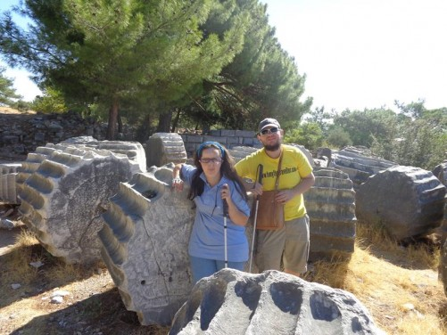 Tony and Tatiana leaning on a large segment of stone column. Other column segments strewn behind.
