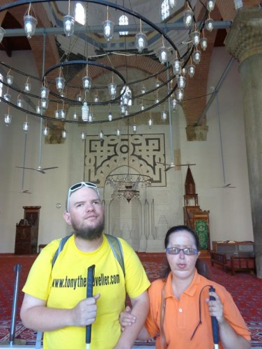 Tony and Tatiana inside the mosque. The mosque's dome partially visible above.
